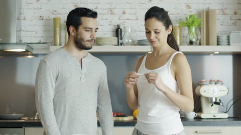 On the Kitchen Beautiful Girl Shows Pregnancy Test Result to Her Boyfriend and they Embrace. Both are very Happy. Shot on RED Cinema Camera in 4K (UHD).