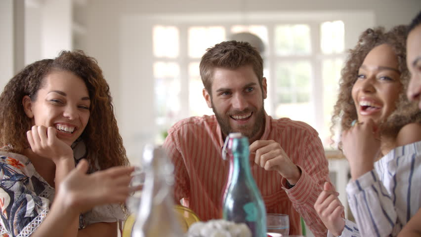 Panning shot of young adult friends talking at dining table