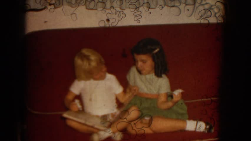 IZMIR TURKEY 1962: young girls looking at a picture book together.