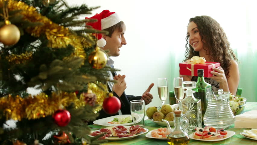 Man Giving Present To Woman During Christmas Dinner In Home