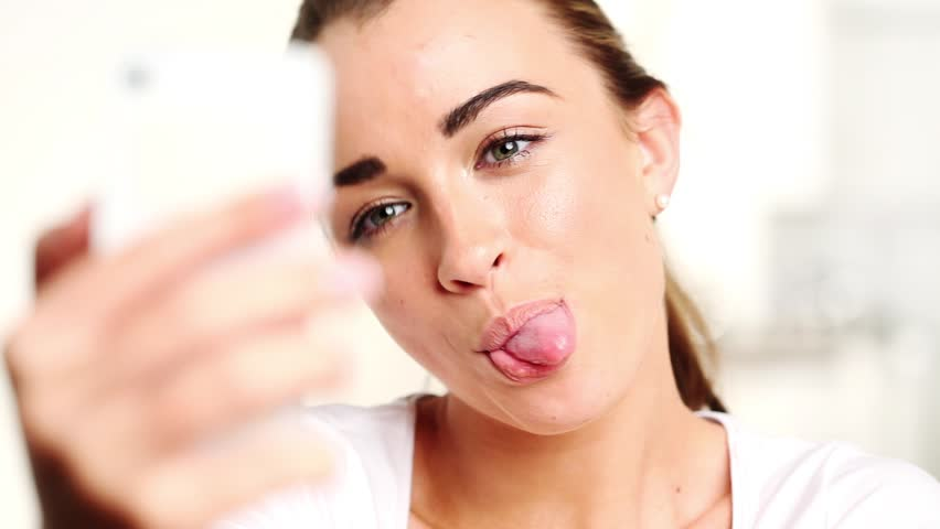 Funny girl taking photographs of herself with mobile phone at home