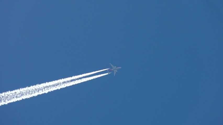 Condensation vapour trails are left behind from a passing airplane.