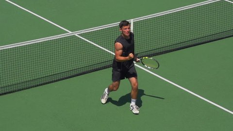 Tennis Player volleys close to net and celebrates.