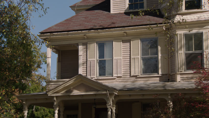 Day holds up upstairs windows above door porch then pans right turret window beige wood clapboard house , bay windows, autumn, fall trees (Oct 2012)