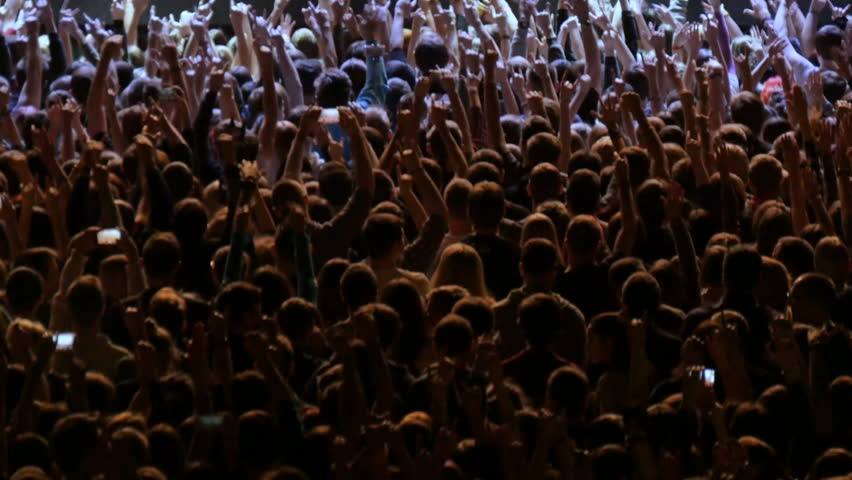 A crowd of people at a rock concert. Fans gather in front of the performance of a rock band.