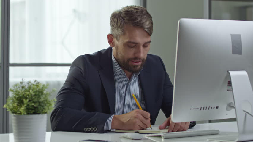 Mid-adult businessman video calling on his computer in the office and writing down something in his organizer