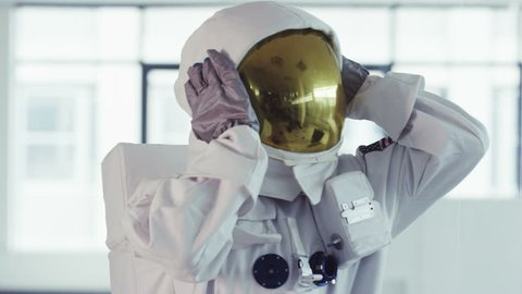 4KAstronaut working in room full of computers takes off helmet and puts it on desk (UK-Oct 2016)
