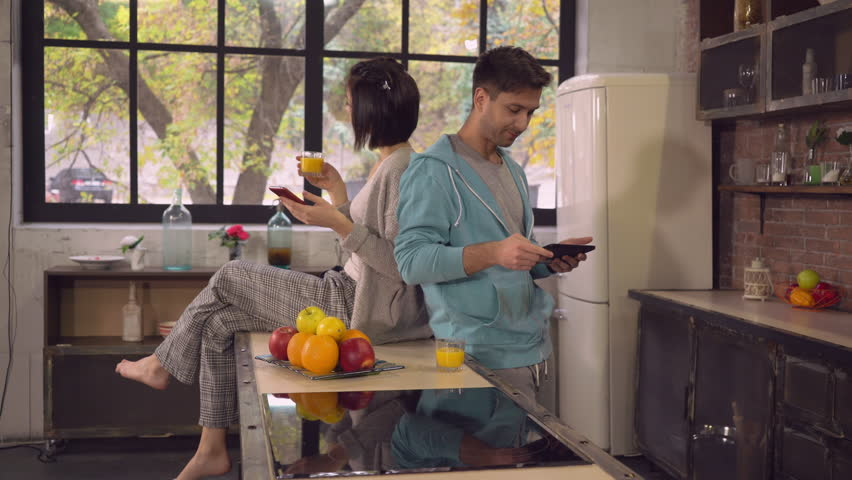 Busy young people have breakfast at home. Caucasian woman drinking orange juice using mobile phone. guy using tablet chatting in social net or surfing internet reading news. Modern family working in