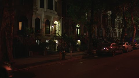 night eastern residential street row nice eastern step up apartments brownstones, white row house bay window basement then pans left,