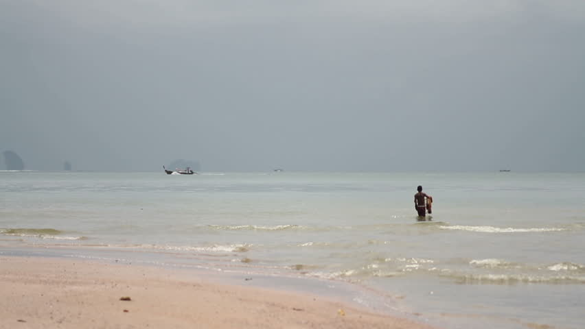 Ao Nang, Krabi Province, Thailand - October 27 2015: fisherman with nets in the background longtail boat floats  | Shutterstock HD Video #21907213