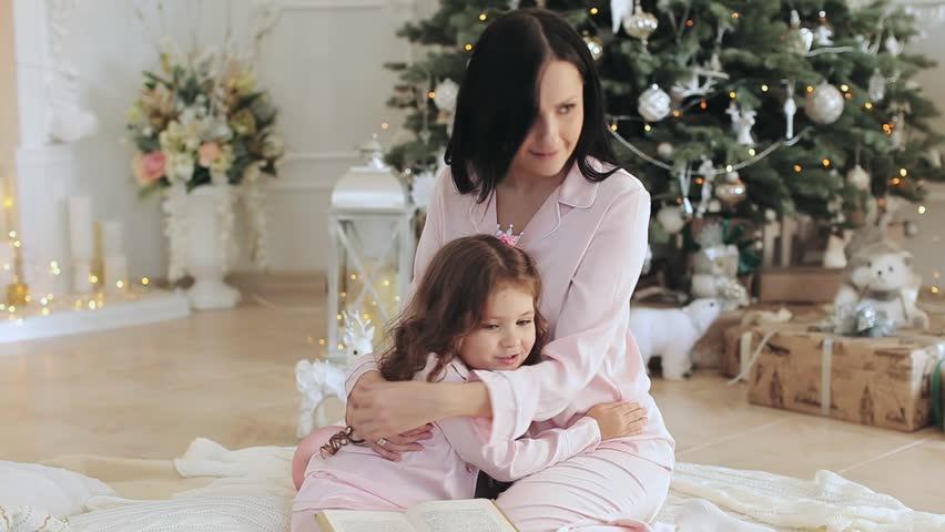 Mother and daughter in pajamas near the Christmas tree | Shutterstock HD Video #21914353