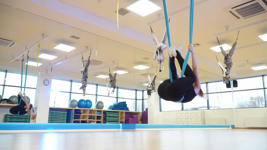 Slow motion, girl hanging upside down on a hammock to fly yoga and does twine