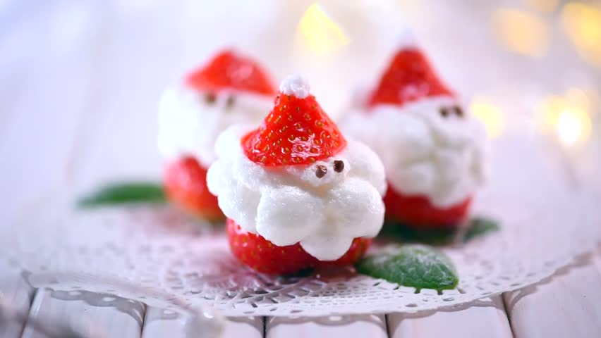 Christmas Strawberry Santa Dessert stuffed with whipped cream. Funny Winter New year Gourmet food. Cheesecake. Xmas party food idea, dinner table setting.
