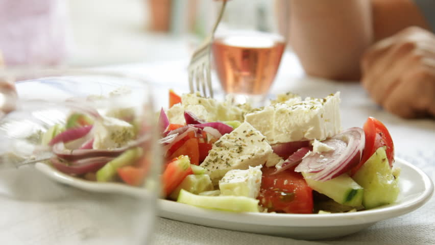 Table setting in restaurant with Greek salad and wine