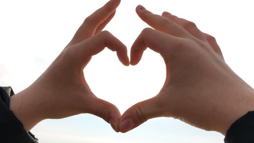 Sun shining through heart shaped hands