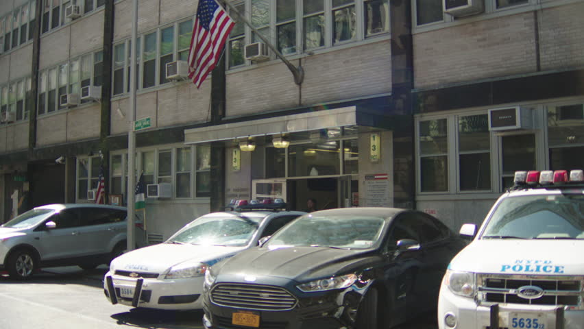 day tight entrance New York Police Station 13th Precinct, tan brick black lines, small silver overhang, parked police cars regular cars, policewoman out