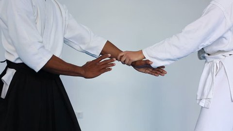 Martial arts master in black hakama practice Aikido with a woman