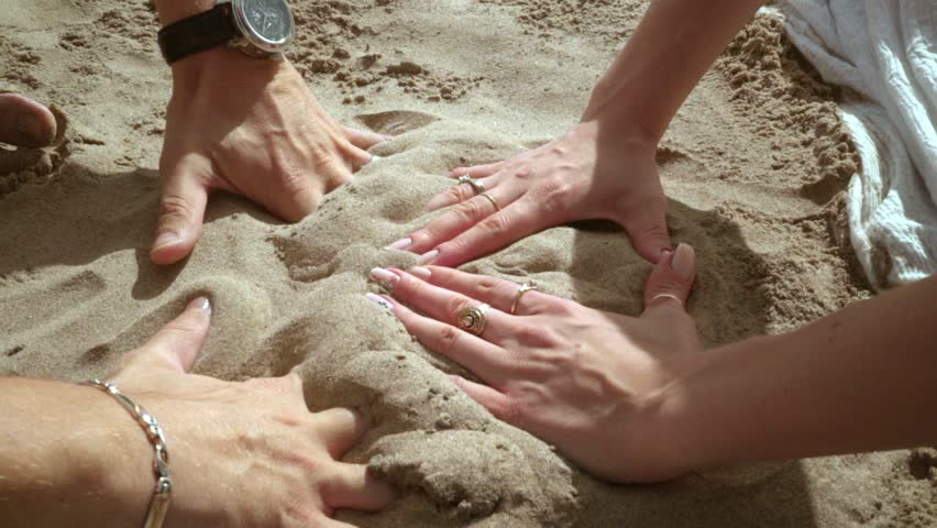 Hands forming heart. Couple hands forming heart shape on sand. People having fun with sand on beach. Love couple hands on summer vacation