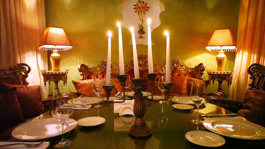 Five candles burn in table center in restaurant lounge