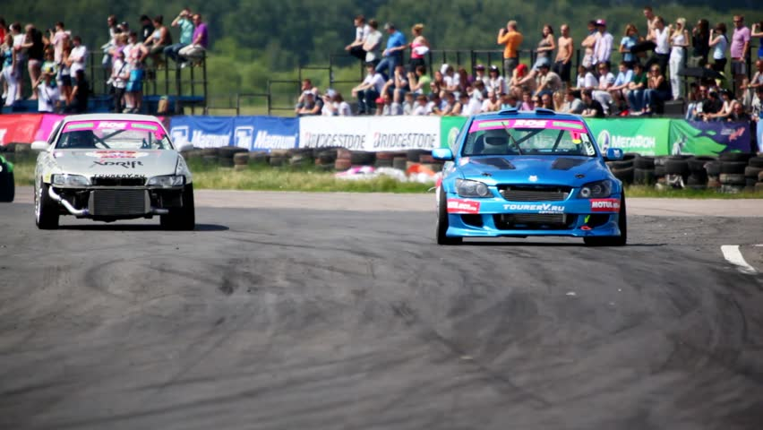 MOSCOW - JUN 11: Three racing cars enter into turn in front of tribunes with audience, on 3rd stage of championship on drift Megafon-RDS 2011, on Jun 11, 2011 in Moscow, Russia