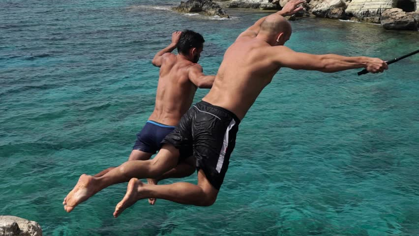 CYPRUS, CIRCA 2016: Two people jump from high cliffs into the sea. Slow motion