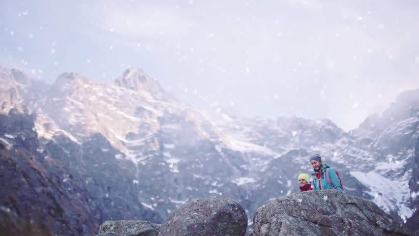 Hikers Reaching Mountain Top. SLOW MOTION. Young happy hiking couple cheering, reached the summit. Man and Woman trekking with backpacks in snow capped mountains. Success and achievement concept. | Shutterstock HD Video #22038163