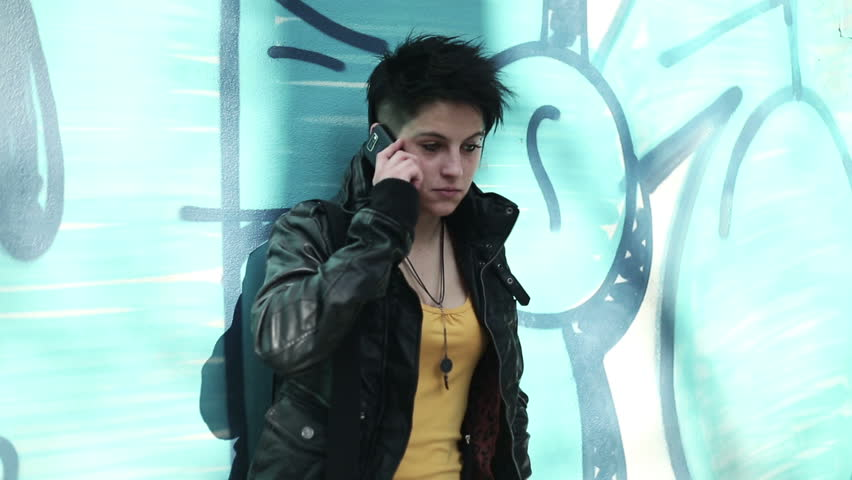 Young punk girl talking on cellphone by the wall | Shutterstock HD Video #2207374