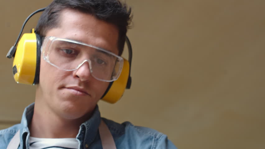 Low angle shot of male carpenter in safety goggles and earmuffs using mechanical sander in workshop