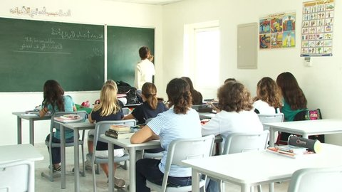Dubai, UAE - circa 2013 - Scene of young primary schoolgirls listening while the teacher is at the blackboard teaching an Arabic language grammar class, in a Dubai primary school. (Dubai, UAE-2013)