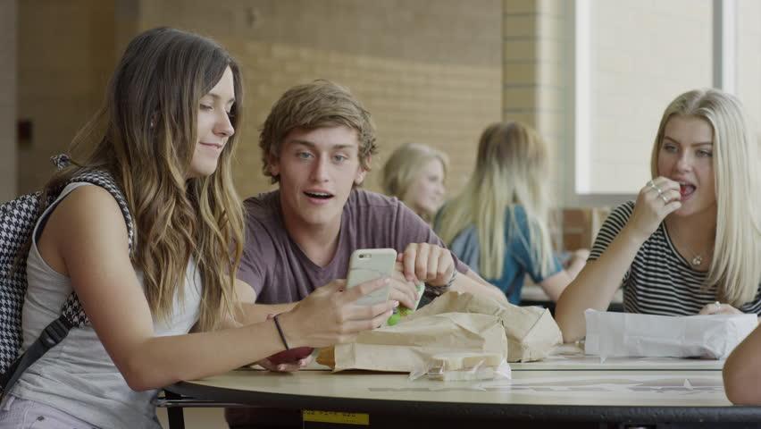 Medium shot of students examining cell phone in school cafeteria / Mapleton, Utah, United States
