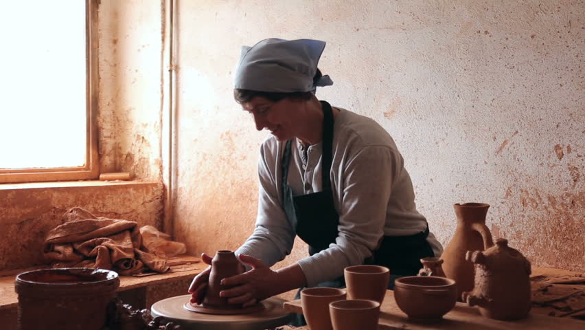 Smiling female  potter working at workshop