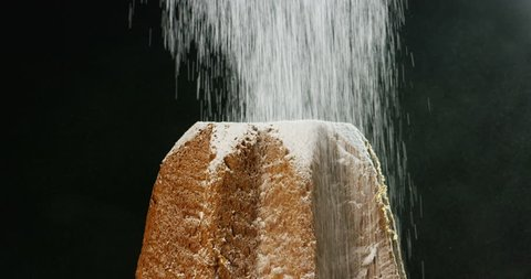 close up of a Pandoro, a typical Italian pastry eaten during the Christmas holidays and the New Year, The powdered sugar falls in slow motion on Pandora creating the Christmas magic.