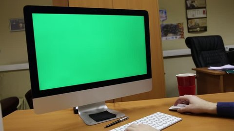 static shot of a man in his home office typing on the keypad in front of a green screen computer display