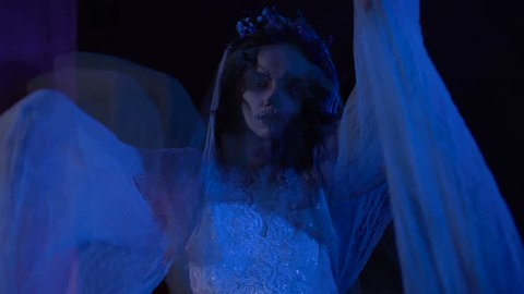 Horror scene from the film with dead girl in white wedding dress and veil. Creepy visual hallucination in the form of changing images of young girl with skull mask on her face.