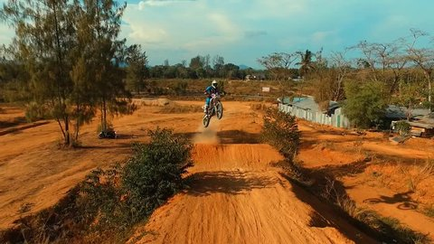 Aerial: Jump on motocross track. Slow motion.