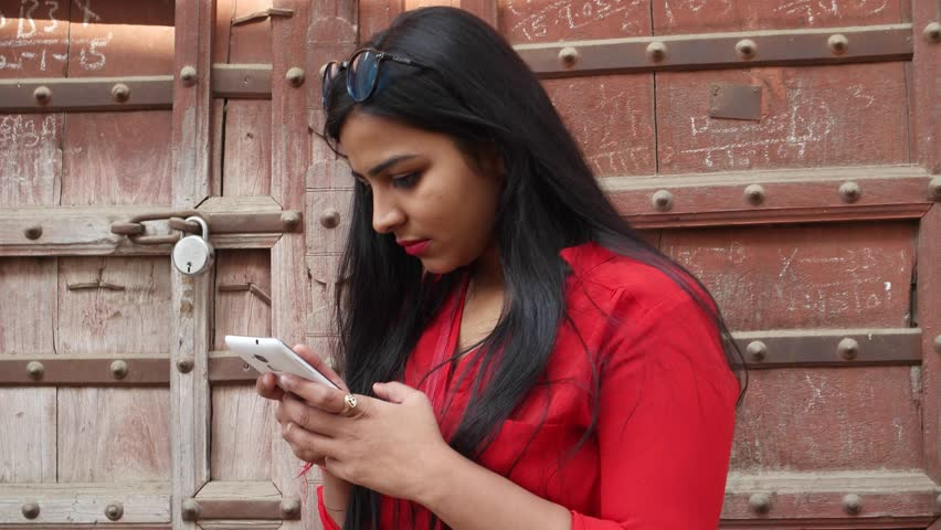 Indian young woman using a cell phone mobile device in Rajasthan, India