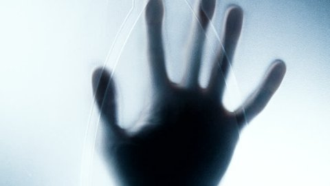 Horror movie scene: hand silhouette behind the window. Hand hits the matte glass surface and slowly sinking on the way down. UHD video 3840x2160.