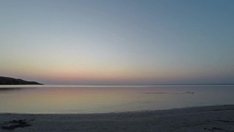 Sunrise on the clear sky in the calm sea. Light cirrus clouds, sandy beach, gulls, birds, insects. Time lap