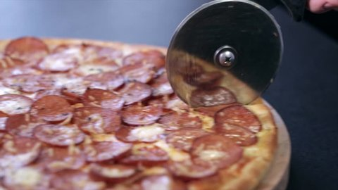 Pizza with salami cut in half with a special knife for pizza. The camera moves in sync with the knife.
