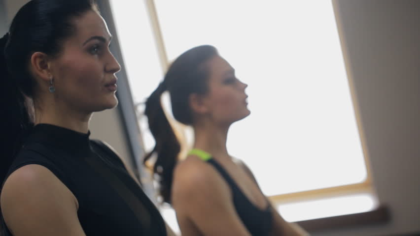 Two women in sports a black suit with a dumbbell swing arm muscles | Shutterstock HD Video #22182553