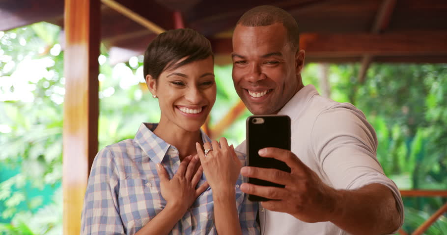 A black couple takes a selfie to celebrate their engagement. An African American man and woman take a picture using a smart phone of her new wedding ring. 4k