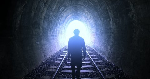 Man goes by railway tracks through dark tunnel toward bright light in the end