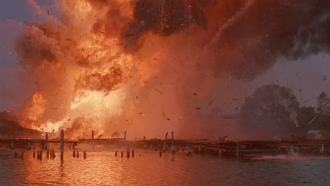 day night DUSK Wide Across water exploding docked cargo industrial ship, huge fireball, blazing fire Two men dock jump into water More explosions lot black smoke disaster, arson, news footage,