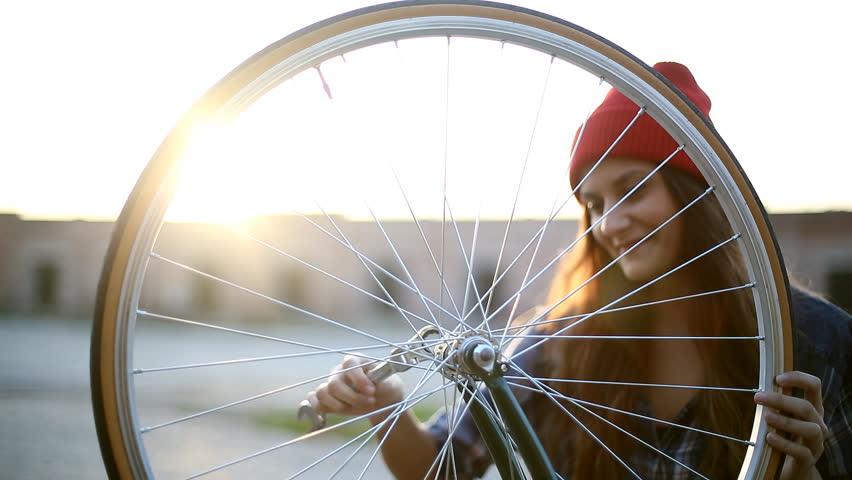 Young woman fixing bicycle wheel | Shutterstock HD Video #22212523
