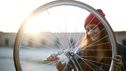 Young woman fixing bicycle wheel