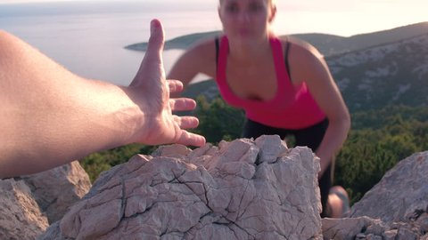 Closeup of a male's hand stretching out and helping female friend reach the mountain top by pulling her up. POV of a man giving hand to a woman climbing on the mountain and helping her reach the top