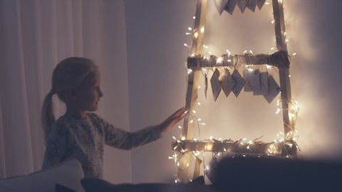MED Little adorable girl passing by hand made advent calendar at her apartment, touching hanging envelopes. 4K UHD RAW edited footage, 60 fps slow motion