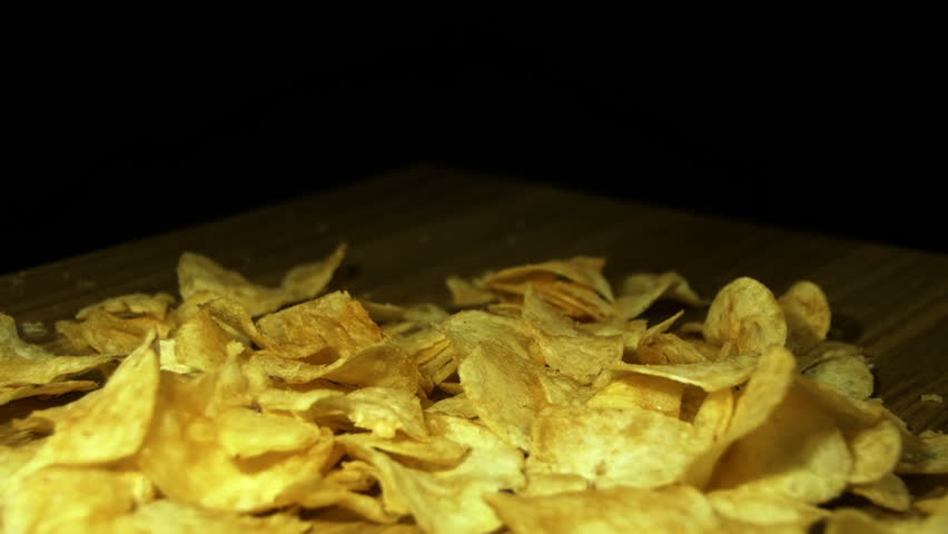 Potato Chips are Falling on a Wooden Table on Black Background. Slow Motion in 96 fps. Potato chips are rotated on a black background. Close-up of yellow delicious chips randomly lying at the table | Shutterstock HD Video #22231273