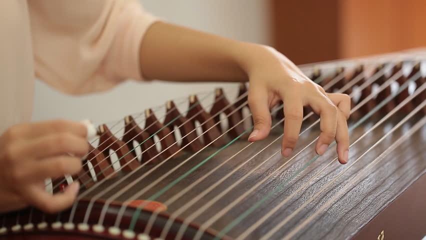 Hand of woman playing guzheng.