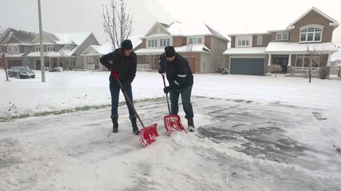 A husband and wife work together to finish shoveling their driveway, and celebrate with a high-five.